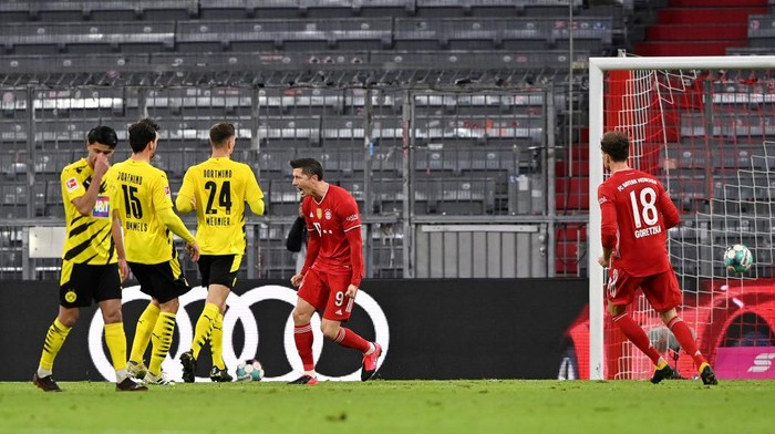 MUNICH, GERMANY - MARCH 06: Robert Lewandowski of FC Bayern Muenchen  celebrates after scoring their teams second goal during the Bundesliga match between FC Bayern Muenchen and Borussia Dortmund at Allianz Arena on March 06, 2021 in Munich, Germany. Sporting stadiums around Germany remain under strict restrictions due to the Coronavirus Pandemic as Government social distancing laws prohibit fans inside venues resulting in games being played behind closed doors. (Photo by Sebastian Widmann/Getty Images)