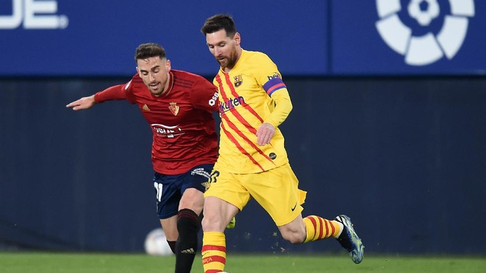 PAMPLONA, SPAIN - MARCH 06: Lionel Messi of FC Barcelona and Kike Barja of C.A. Osasuna  battle for the ball  during the La Liga Santander match between C.A. Osasuna and FC Barcelona at Estadio El Sadar on March 06, 2021 in Pamplona, Spain. Sporting stadiums around Spain remain under strict restrictions due to the Coronavirus Pandemic as Government social distancing laws prohibit fans inside venues resulting in games being played behind closed doors.  (Photo by Juan Manuel Serrano Arce/Getty Images)