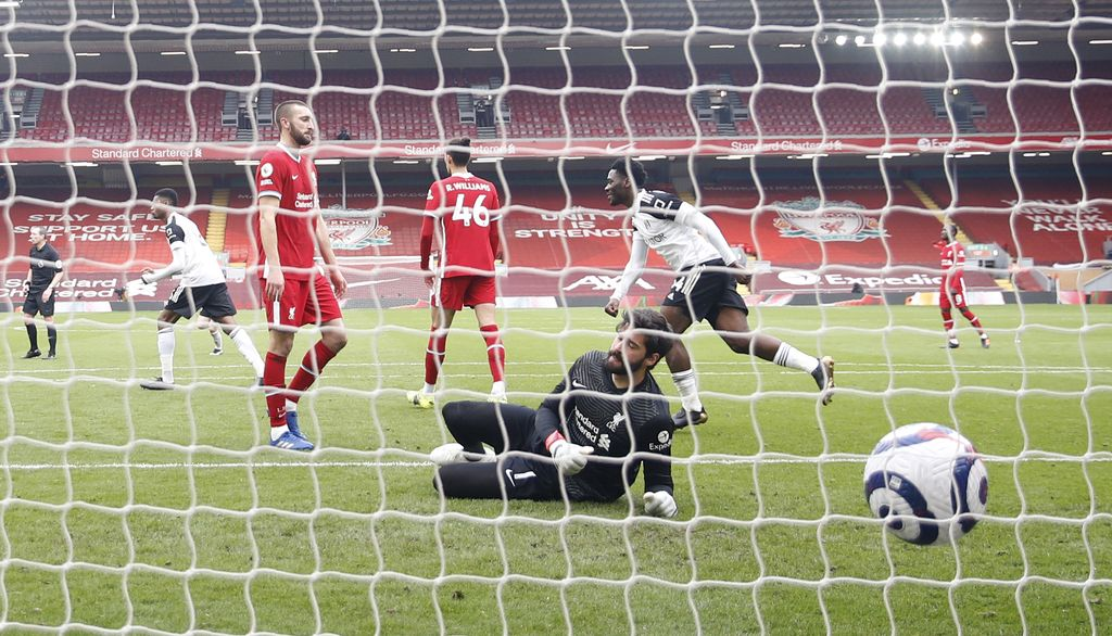 Liverpool's goalkeeper Alisson fails to save the goal from Fulham's Mario Lemina during the English Premier League soccer match between Liverpool and Fulham at Anfield stadium in Liverpool, England, Sunday, March 7, 2021. (Phil Noble/Pool via AP)