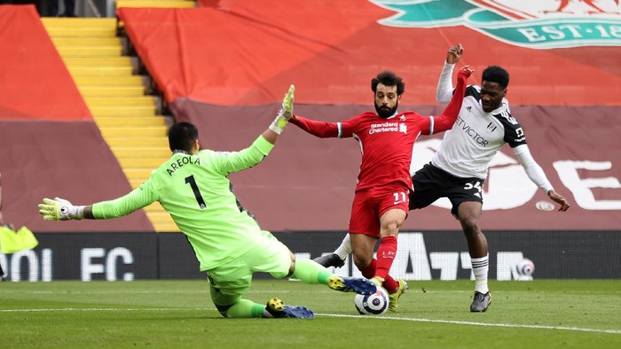 LIVERPOOL, ENGLAND - MARCH 07: Mohamed Salah of Liverpool is challenged by Alphonse Areola and Ola Aina of Fulham during the Premier League match between Liverpool and Fulham at Anfield on March 07, 2021 in Liverpool, England. Sporting stadiums around the UK remain under strict restrictions due to the Coronavirus Pandemic as Government social distancing laws prohibit fans inside venues resulting in games being played behind closed doors. (Photo by Clive Brunskill/Getty Images)