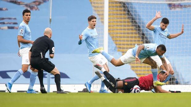 MANCHESTER, ENGLAND - MARCH 07: Anthony Martial of Manchester United is fouled by Gabriel Jesus and Ruben Dias of Manchester City in the box leading to a penalty being given during the Premier League match between Manchester City and Manchester United at Etihad Stadium on March 07, 2021 in Manchester, England. Sporting stadiums around the UK remain under strict restrictions due to the Coronavirus Pandemic as Government social distancing laws prohibit fans inside venues resulting in games being played behind closed doors. (Photo by Dave Thompson - Pool/Getty Images)
