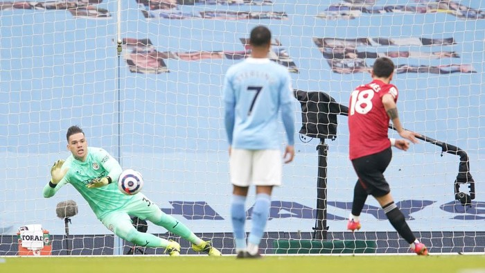MANCHESTER, ENGLAND - MARCH 07: Bruno Fernandes of Manchester United scores their sides first goal past Ederson of Manchester City from the penalty spot during the Premier League match between Manchester City and Manchester United at Etihad Stadium on March 07, 2021 in Manchester, England. Sporting stadiums around the UK remain under strict restrictions due to the Coronavirus Pandemic as Government social distancing laws prohibit fans inside venues resulting in games being played behind closed doors. (Photo by Dave Thompson - Pool/Getty Images)