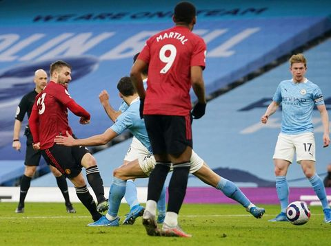 MANCHESTER, ENGLAND - MARCH 07: Luke Shaw of Manchester United scores their sides second goal during the Premier League match between Manchester City and Manchester United at Etihad Stadium on March 07, 2021 in Manchester, England. Sporting stadiums around the UK remain under strict restrictions due to the Coronavirus Pandemic as Government social distancing laws prohibit fans inside venues resulting in games being played behind closed doors. (Photo by Dave Thompson - Pool/Getty Images)