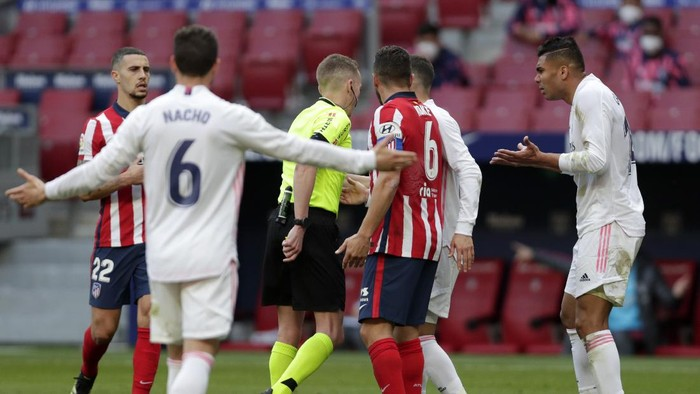 Real Madrids Nacho, left, and Casemiro, right, open their arms as they take on the referee during the Spanish La Liga soccer match between Atletico Madrid and Real Madrid at the Wanda Metropolitano stadium in Madrid, Spain, Sunday, March 7, 2021. (AP Photo/Manu Fernandez)