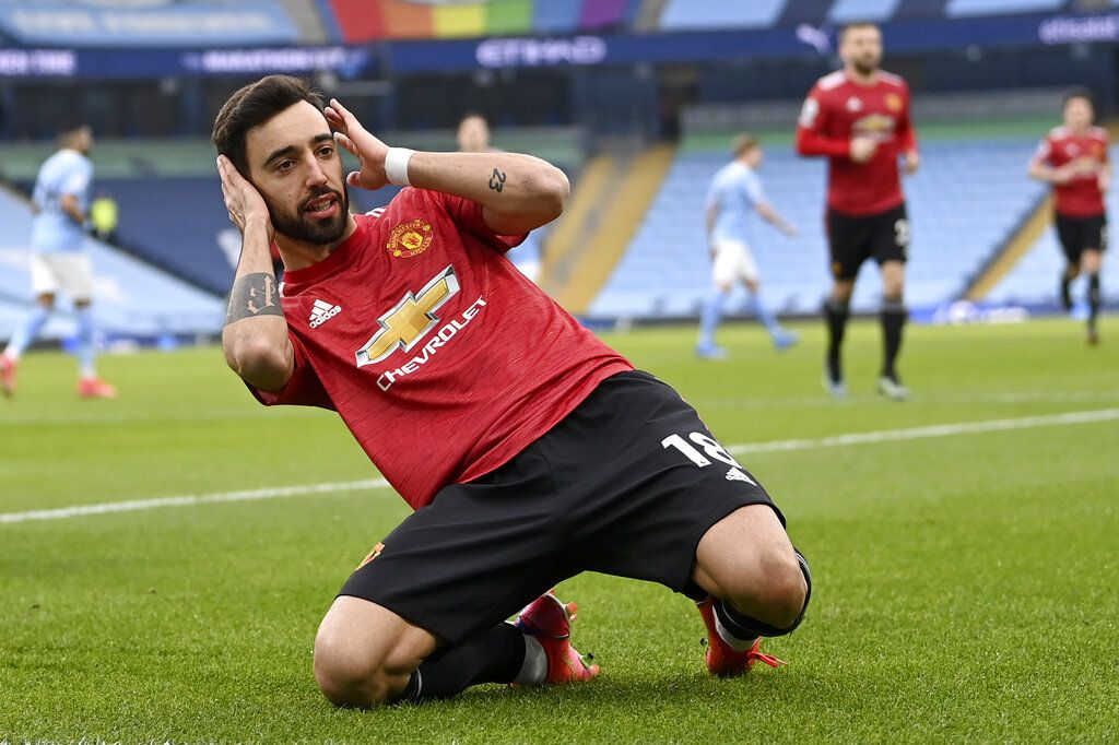 Manchester United's Bruno Fernandes celebrates after scoring the opening goal during the English Premier League soccer match between Manchester City and Manchester United at the Etihad Stadium in Manchester, England, Sunday, March 7, 2021. (Laurence Griffiths/Pool via AP)