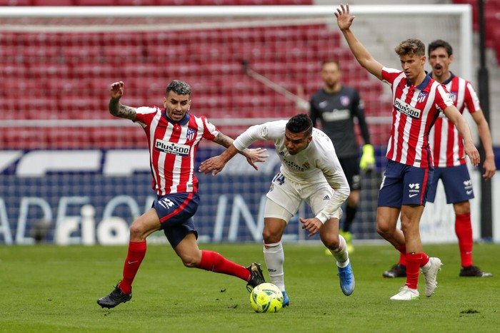 Atletico Madrids Angel Correa, left, and Real Madrids Casemiro vie for the ball during the Spanish La Liga soccer match between Atletico Madrid and Real Madrid at the Wanda Metropolitano stadium in Madrid, Spain, Sunday, March 7, 2021. (AP Photo/Manu Fernandez)