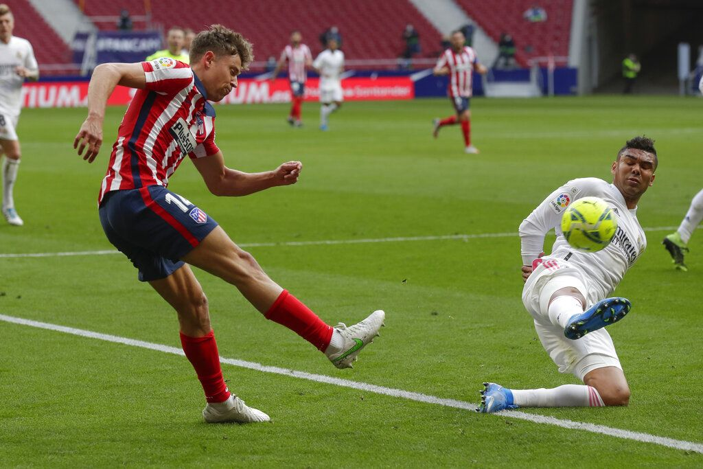 Atletico Madrid's Angel Correa, left, and Real Madrid's Casemiro vie for the ball during the Spanish La Liga soccer match between Atletico Madrid and Real Madrid at the Wanda Metropolitano stadium in Madrid, Spain, Sunday, March 7, 2021. (AP Photo/Manu Fernandez)