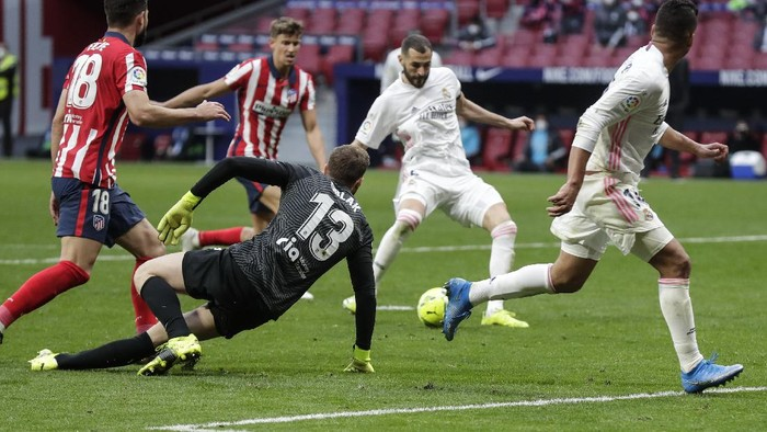 Real Madrids Karim Benzema scores his sides opening goal during the Spanish La Liga soccer match between Atletico Madrid and Real Madrid at the Wanda Metropolitano stadium in Madrid, Spain, Sunday, March 7, 2021. (AP Photo/Manu Fernandez)