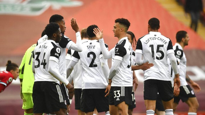 Fulham players celebrate at the end of the English Premier League soccer match between Liverpool and Fulham at Anfield stadium in Liverpool, England, Sunday, March 7, 2021. (Paul Ellis/Pool via AP)