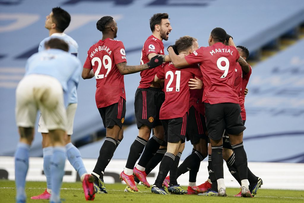 Manchester United players celebrate after scoring their second goal during the English Premier League soccer match between Manchester City and Manchester United at the Etihad Stadium in Manchester, England, Sunday, March 7, 2021. (Dave Thompson/Pool via AP)