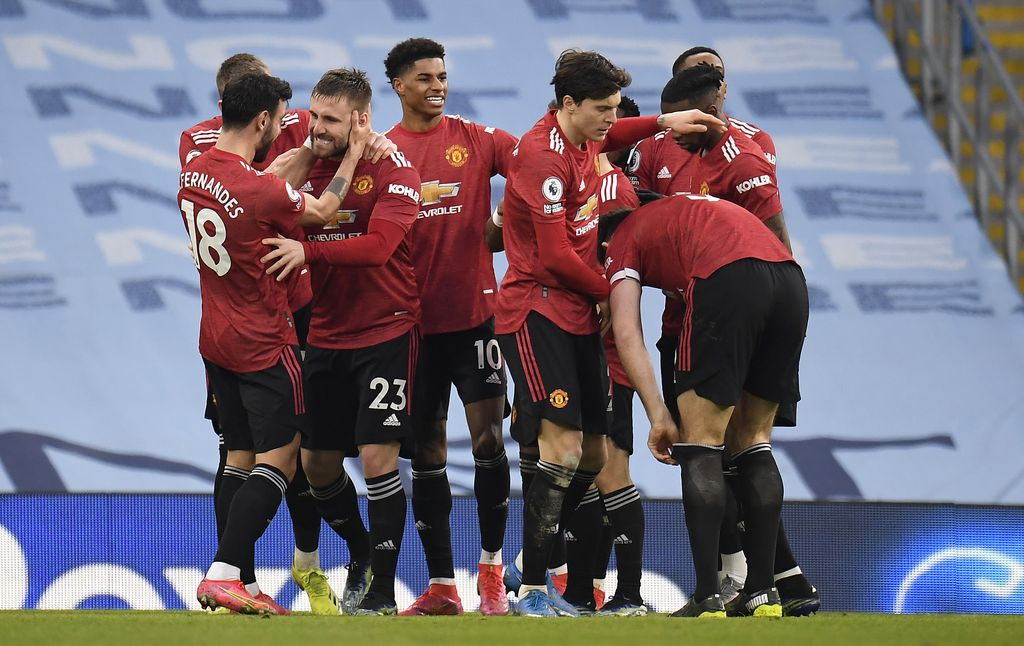 MANCHESTER, ENGLAND - MARCH 07: Luke Shaw of Manchester United celebrates with Bruno Fernandes, Marcus Rashford and team mates after scoring their side's second goal during the Premier League match between Manchester City and Manchester United at Etihad Stadium on March 07, 2021 in Manchester, England. Sporting stadiums around the UK remain under strict restrictions due to the Coronavirus Pandemic as Government social distancing laws prohibit fans inside venues resulting in games being played behind closed doors. (Photo by Peter Powell - Pool/Getty Images)