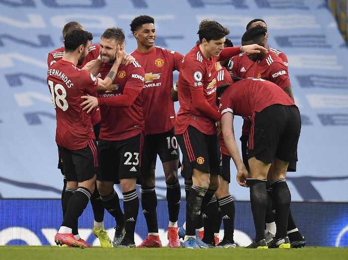 MANCHESTER, ENGLAND - MARCH 07: Luke Shaw of Manchester United celebrates with Bruno Fernandes, Marcus Rashford and team mates after scoring their sides second goal during the Premier League match between Manchester City and Manchester United at Etihad Stadium on March 07, 2021 in Manchester, England. Sporting stadiums around the UK remain under strict restrictions due to the Coronavirus Pandemic as Government social distancing laws prohibit fans inside venues resulting in games being played behind closed doors. (Photo by Peter Powell - Pool/Getty Images)