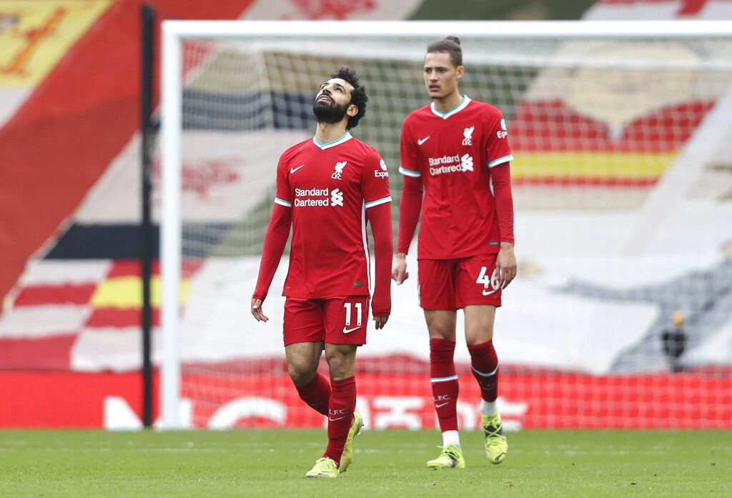 Liverpool's Mohamed Salah and Liverpool's Rhys Williams react after Fulham's Mario Lemina scored his side's first goal during the English Premier League soccer match between Liverpool and Fulham at Anfield stadium in Liverpool, England, Sunday, March 7, 2021. (Clive Brunskill/Pool via AP)