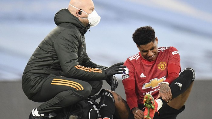 MANCHESTER, ENGLAND - MARCH 07: Marcus Rashford of Manchester United reacts as he receives medical treatment during the Premier League match between Manchester City and Manchester United at Etihad Stadium on March 07, 2021 in Manchester, England. Sporting stadiums around the UK remain under strict restrictions due to the Coronavirus Pandemic as Government social distancing laws prohibit fans inside venues resulting in games being played behind closed doors. (Photo by Peter Powell - Pool/Getty Images)