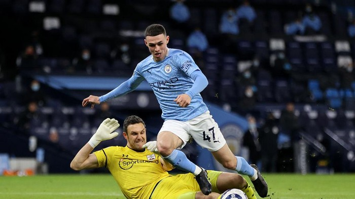 MANCHESTER, ENGLAND - MARCH 10: Phil Foden of Manchester City is challenged by Alex McCarthy of Southampton during the Premier League match between Manchester City and Southampton at Etihad Stadium on March 10, 2021 in Manchester, England. Sporting stadiums around the UK remain under strict restrictions due to the Coronavirus Pandemic as Government social distancing laws prohibit fans inside venues resulting in games being played behind closed doors. (Photo by Clive Brunskill/Getty Images)