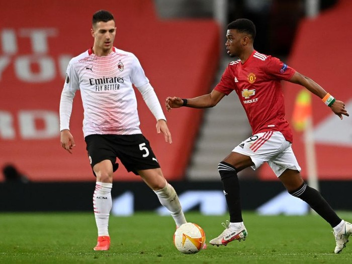 MANCHESTER, ENGLAND - MARCH 11: Amad Diallo of Manchester United runs with the ball under pressure from Diogo Dalot of A.C. Milan during the UEFA Europa League Round of 16 First Leg match between Manchester United and A.C. Milan at Old Trafford on March 11, 2021 in Manchester, England. Sporting stadiums around the UK remain under strict restrictions due to the Coronavirus Pandemic as Government social distancing laws prohibit fans inside venues resulting in games being played behind closed doors. (Photo by Laurence Griffiths/Getty Images)