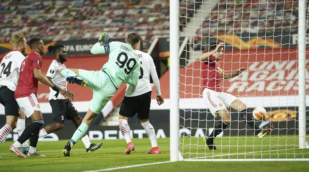 Manchester United's Harry Maguire, right, makes an attempt to score during the Europa League round of 16 first leg soccer match between Manchester United and AC Milan at Old Trafford in Manchester, England, Thursday, March 11, 2021. (AP Photo/Dave Thompson)