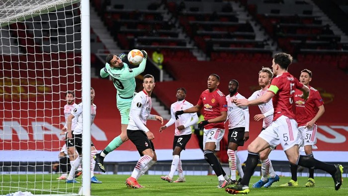 MANCHESTER, ENGLAND - MARCH 11: Gianluigi Donnarumma of A.C. Milan makes a save leading to a missed chance for Harry Maguire of Manchester United during the UEFA Europa League Round of 16 First Leg match between Manchester United and A.C. Milan at Old Trafford on March 11, 2021 in Manchester, England. Sporting stadiums around the UK remain under strict restrictions due to the Coronavirus Pandemic as Government social distancing laws prohibit fans inside venues resulting in games being played behind closed doors. (Photo by Laurence Griffiths/Getty Images)