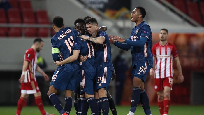 Arsenals Martin Odegaard, second right, celebrates with teammates after scoring the opening goal during the Europa League round of 16, first leg, soccer match between Olympiacos and Arsenal at Georgios Karaiskakis stadium, in Piraeus port, near Athens, Thursday, March 11, 2021. (AP Photo/Thanassis Stavrakis)