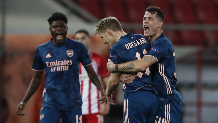 Arsenals Martin Odegaard, centre celebrates with teammates after scoring the opening goal during the Europa League round of 16, first leg, soccer match between Olympiacos and Arsenal at Georgios Karaiskakis stadium, in Piraeus port, near Athens, Thursday, March 11, 2021. (AP Photo/Thanassis Stavrakis)