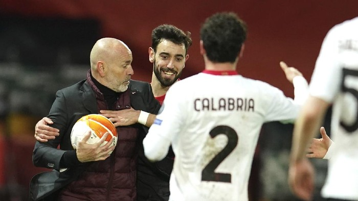 AC Milans manager Stefano Pioli, left, and Manchester Uniteds Bruno Fernandes during the Europa League round of 16 first leg soccer match between Manchester United and AC Milan at Old Trafford in Manchester, England, Thursday, March 11, 2021. (AP Photo/Dave Thompson)