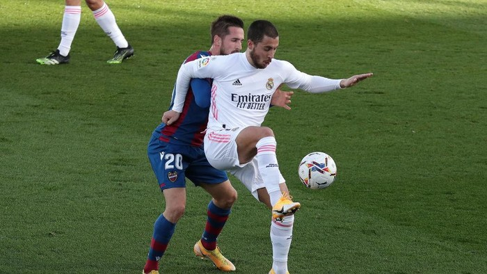 MADRID, SPAIN - JANUARY 30: Eden Hazard of Real Madrid is challenged by Jorge Miramon of Levante UD during the La Liga Santander match between Real Madrid and Levante UD at Estadio Alfredo Di Stefano on January 30, 2021 in Madrid, Spain. Sporting stadiums around Spain remain under strict restrictions due to the Coronavirus Pandemic as Government social distancing laws prohibit fans inside venues resulting in games being played behind closed doors. (Photo by Gonzalo Arroyo Moreno/Getty Images)