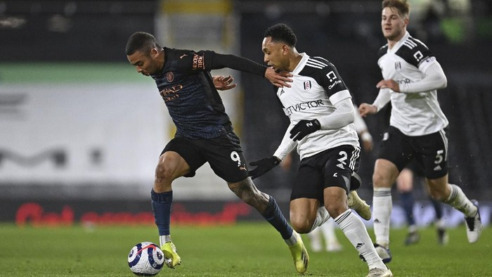 Manchester Citys Gabriel Jesus, left holds off Fulhams Kenny Tete during an English Premier League soccer match between Fulham and Manchester City at the Craven Cottage stadium in London, England, Saturday March 13, 2021. (Justin Setterfield/Pool via AP)