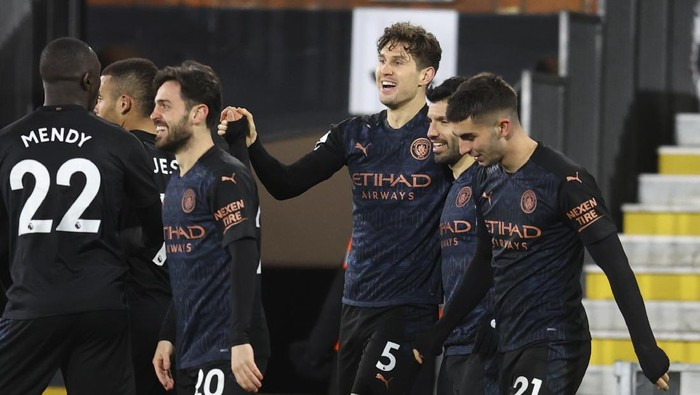 Manchester Citys John Stones, centre, celebrates with team mates after scoring his sides opening goal during an English Premier League soccer match between Fulham and Manchester City at the Craven Cottage stadium in London, England, Saturday March 13, 2021. (Catherine Ivill/Pool via AP)