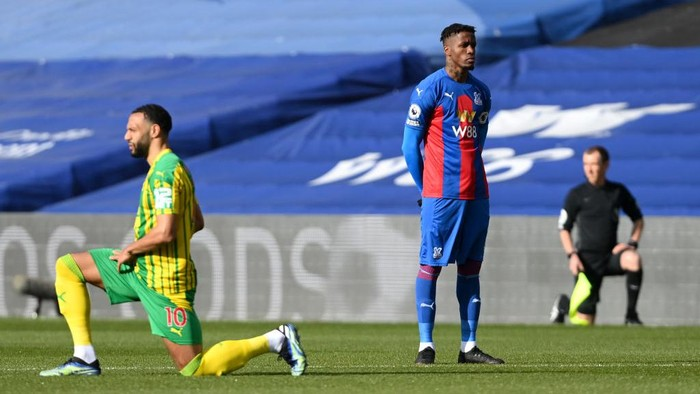 LONDON, ENGLAND - MARCH 13: Wilfried Zaha of Crystal Palace stands at kick off as Matt Phillips of West Bromwich Albion takes a knee in support of the Black Lives Matter movement prior to the Premier League match between Crystal Palace and West Bromwich Albion at Selhurst Park on March 13, 2021 in London, England. Sporting stadiums around the UK remain under strict restrictions due to the Coronavirus Pandemic as Government social distancing laws prohibit fans inside venues resulting in games being played behind closed doors. (Photo by Mike Hewitt/Getty Images)
