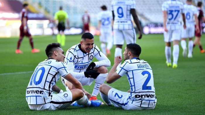 TURIN, ITALY - MARCH 14: Lautaro Martinez (L) of Internazionale celebrates with team mates (L - R) Alexis Sanchez and Achraf Hakimi after scoring their sides second goal during the Serie A match between Torino FC  and FC Internazionale at Stadio Olimpico di Torino on March 14, 2021 in Turin, Italy. Sporting stadiums around Italy remain under strict restrictions due to the Coronavirus Pandemic as Government social distancing laws prohibit fans inside venues resulting in games being played behind closed doors. (Photo by Valerio Pennicino/Getty Images)
