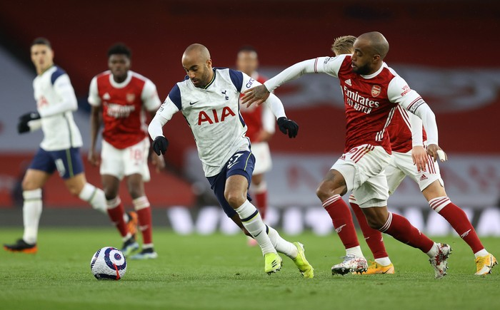 LONDON, ENGLAND - MARCH 14: Lucas Moura of Tottenham Hotspur is challenged by Alexandre Lacazette of Arsenal during the Premier League match between Arsenal and Tottenham Hotspur at Emirates Stadium on March 14, 2021 in London, England. Sporting stadiums around the UK remain under strict restrictions due to the Coronavirus Pandemic as Government social distancing laws prohibit fans inside venues resulting in games being played behind closed doors. (Photo by Julian Finney/Getty Images)