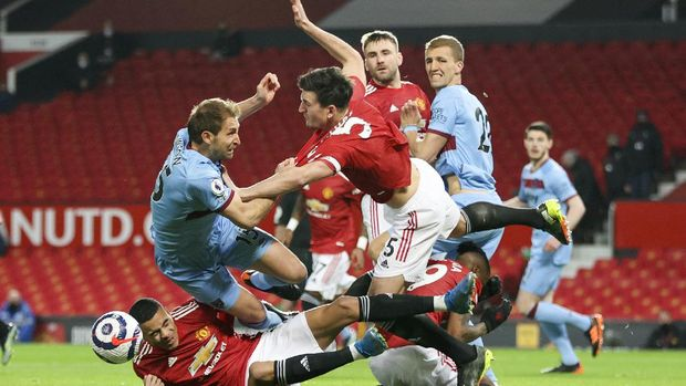 West Ham's Craig Dawson, left, and Manchester United's Harry Maguire compete for the ball during the English Premier League soccer match between Manchester United and West Ham United at Old Trafford, Manchester, England, Sunday, March. 14, 2021. (AP Photo/Clive Brunskill,Pool)