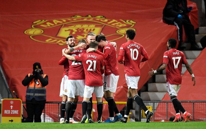 MANCHESTER, ENGLAND - MARCH 14: Scott McTominay of Manchester United celebrates with Bruno Fernandes and team mates after their side's first goal, an own goal scored by Craig Dawson (Not pictured) of West Ham United during the Premier League match between Manchester United and West Ham United at Old Trafford on March 14, 2021 in Manchester, England. Sporting stadiums around the UK remain under strict restrictions due to the Coronavirus Pandemic as Government social distancing laws prohibit fans inside venues resulting in games being played behind closed doors. (Photo by Peter Powell - Pool/Getty Images)