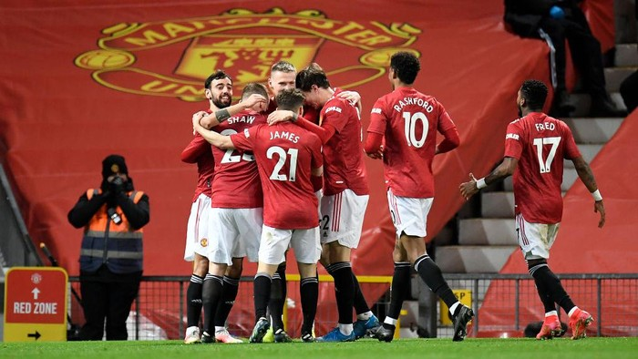MANCHESTER, ENGLAND - MARCH 14: Scott McTominay of Manchester United celebrates with Bruno Fernandes and team mates after their sides first goal, an own goal scored by Craig Dawson (Not pictured) of West Ham United during the Premier League match between Manchester United and West Ham United at Old Trafford on March 14, 2021 in Manchester, England. Sporting stadiums around the UK remain under strict restrictions due to the Coronavirus Pandemic as Government social distancing laws prohibit fans inside venues resulting in games being played behind closed doors. (Photo by Peter Powell - Pool/Getty Images)