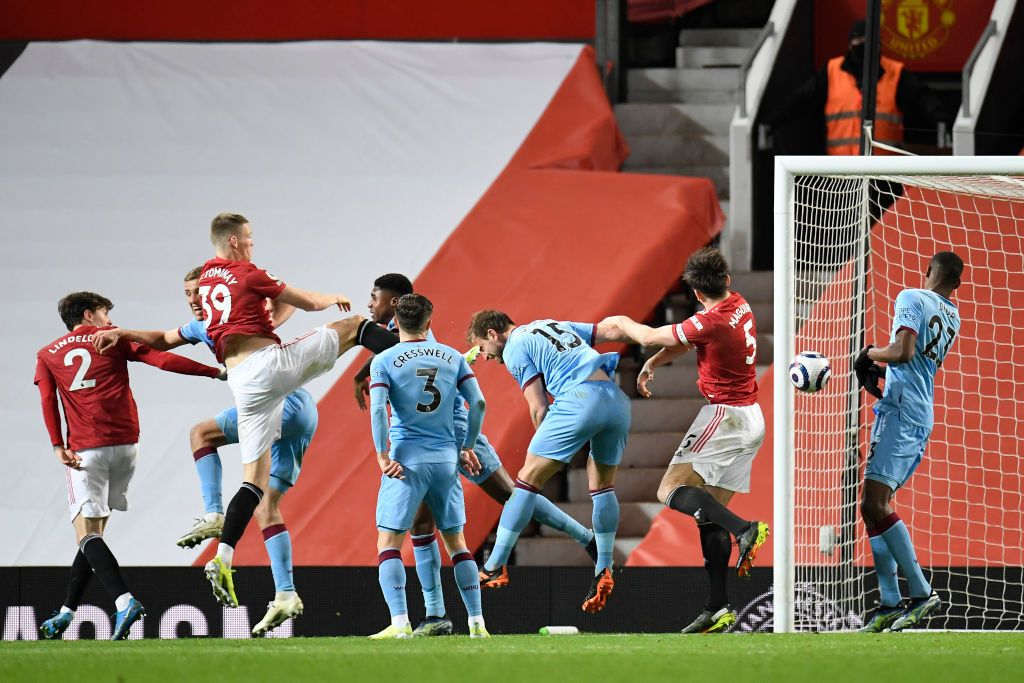 MANCHESTER, ENGLAND - MARCH 14: Craig Dawson of West Ham United scores an own goal for Manchester United's first goal whilst under pressure from Scott McTominay of Manchester United during the Premier League match between Manchester United and West Ham United at Old Trafford on March 14, 2021 in Manchester, England. Sporting stadiums around the UK remain under strict restrictions due to the Coronavirus Pandemic as Government social distancing laws prohibit fans inside venues resulting in games being played behind closed doors. (Photo by Peter Powell - Pool/Getty Images)