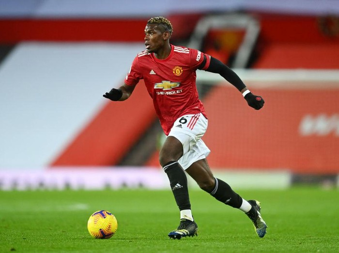 MANCHESTER, ENGLAND - FEBRUARY 06: Paul Pogba of Manchester United runs with the ball during the Premier League match between Manchester United and Everton at Old Trafford on February 06, 2021 in Manchester, England. Sporting stadiums around the UK remain under strict restrictions due to the Coronavirus Pandemic as Government social distancing laws prohibit fans inside venues resulting in games being played behind closed doors. (Photo by Michael Regan/Getty Images)