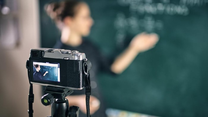 Young teacher teaching remotely using camera to stream lesson.