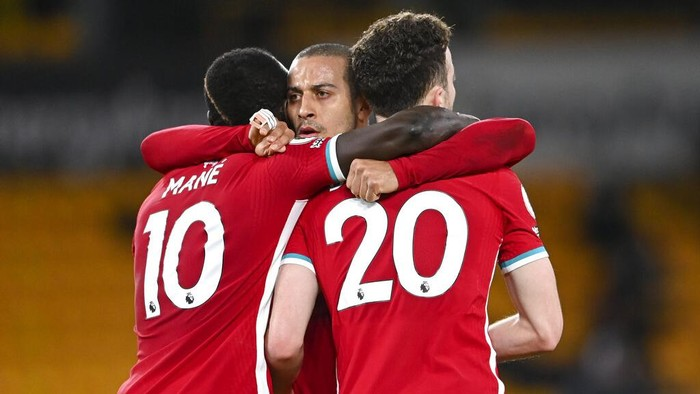 Liverpools Thiago, centre, congratulates teammate Diogo Jota, right, after scoring his teams first goal with Sadio Mane, left, during the English Premier League soccer match between Wolverhampton Wanderers and Liverpool at Molineux Stadium in Wolverhampton, England, Monday, March. 15, 2021. (AP Photo/Laurence Griffiths,Pool)