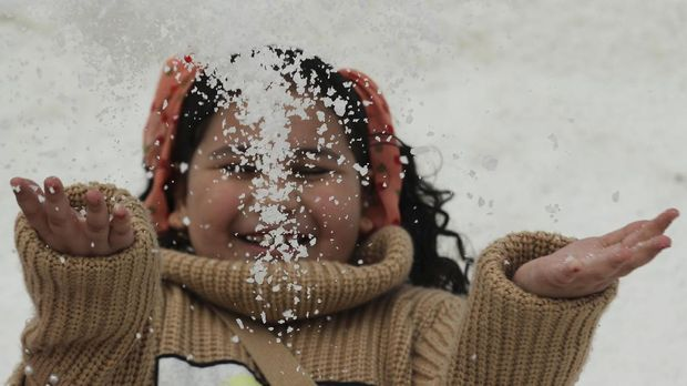 A girl throws up some salt crystals as she visits the small salt hills in the canal city of Port Fouad, Egypt March 12, 2021. Picture taken March 12, 2021. REUTERS/Mohamed Abd El Ghany