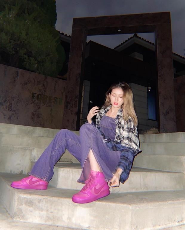 Ia memadukan denim overall berwarna ungu dengan checked oversized shirt dan memasangkannya dengan sepatu AMBUSH x Nike Dunk High berwarna pink.