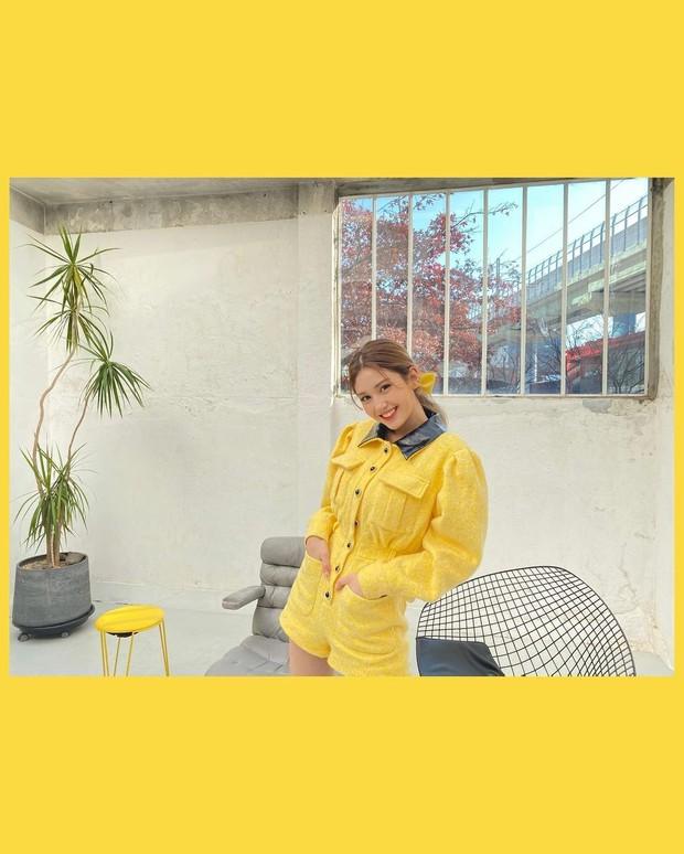 Penampilan Somi yang mengenakan short jumpsuit berwarna kuning memperlihatkan visual dirinya tampak cerah.