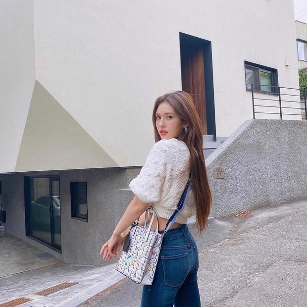 Somi memadukan atasan textured knit cropped cardigan berwarna putih dengan celana jeans. Dengan outfit tersebut penampilan Somi tetap sederhana dan hanya mengkombinasikannya dengan totebag.