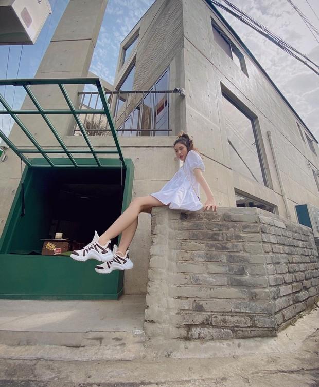 Somi mengenakan voluminous dress berwarna putih yang dipasangkan dengan sneakers dari Louis Vuitton. Outfit ini bisa kamu kenakan saat kencan bersama pasangan kamu.