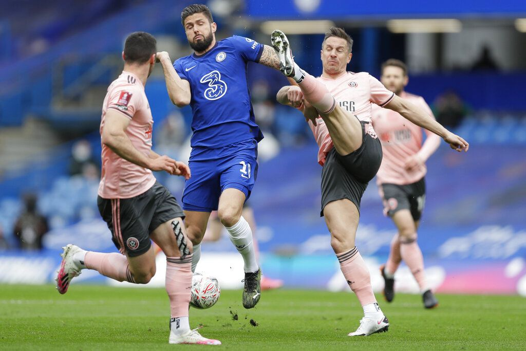 Chelsea's Olivier Giroud, center, is challenged by Sheffield United's Phil Jagielka, right, during the English FA Cup quarterfinal soccer match between Chelsea and Sheffield United at the Stamford Bridge stadium in London, Sunday, March 21, 2021. (AP Photo/Kirsty Wigglesworth)
