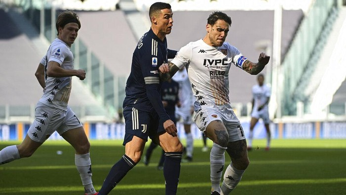 Juventus Cristiano Ronaldo, left, challenges Beneventos Nicolas Viola during the Serie A soccer match between Juventus and Benevento at the Allianz stadium in Turin, Italy, Sunday, March 21, 2021. (Marco Alpozzi/LaPresse via AP)