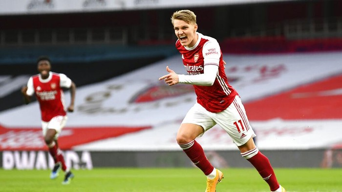 Arsenals Martin Odegaard celebrates after scoring his sides opening goal during the English Premier League soccer match between Arsenal and Tottenham Hotspur at the Emirates stadium in London, England, Sunday, March 14, 2021. (Dan Mullan/Pool via AP)