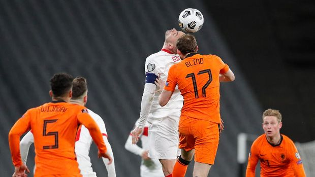 Turkey's forward Burak Yilmaz (C) heads the ball with Netherlands' defender Daley Blind (17) during the FIFA World Cup Qatar 2022 qualification Group G football match between Turkey and The Netherlands at the Ataturk Olympic Stadium, in Istanbul, on March 24, 2021. (Photo by MURAD SEZER / POOL / AFP)