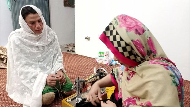 Rani Khan, a transgender woman who teaches the Koran at Pakistan's first transgender only madrasa or a religious school, looks at one of her students during a tailoring lesson in Islamabad, Pakistan March 10, 2021. Picture taken March 10, 2021. REUTERS/Salahuddin NO RESALES. NO ARCHIVES