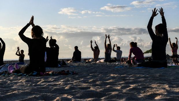 A group of people participate in a yoga session taught by Radha Silva on the beach in Miami Beach, Florida, on March 23, 2021. - Hordes of drunken revellers ignoring the pandemic have forced parts of Miami Beach into a state of emergency but, just blocks away, locals organize trash collection and do yoga in the morning calm. About a dozen early-risers, most of them residents, gather on the beach in front of a lifeguard hut for a yoga class that begins as the sun rises over Florida. (Photo by CHANDAN KHANNA / AFP)