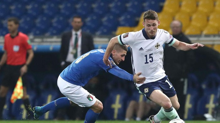 PARMA, ITALY - MARCH 25: Jordan Thompson of Northern Ireland battles for possession with Matteo Pessina of Italy during the FIFA World Cup 2022 Qatar qualifying match between Italy and Northern Ireland on March 25, 2021 in Parma, Italy. Sporting stadiums around Italy remain under strict restrictions due to the Coronavirus Pandemic as Government social distancing laws prohibit fans inside venues resulting in games being played behind closed doors. (Photo by Marco Luzzani/Getty Images)